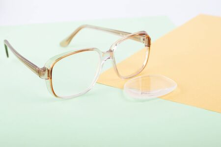broken glasses, lens replacement to improve vision, dropped glass from the frame of glasses close-up