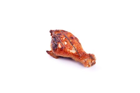 grilled chicken leg with crust on a white background isolated closeup.