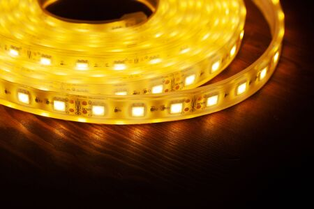 Led silicon shining strip in coil. Diode lights on wooden table closeup Фото со стока