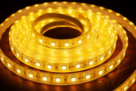 Led silicon shining strip in coil. Diode lights closeup.Warm light.