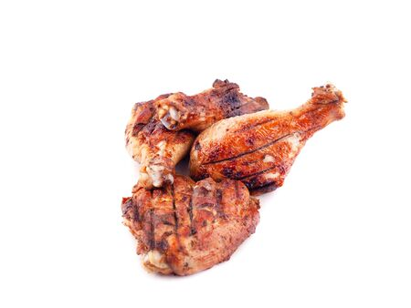 grilled chicken legs with crust on a white background closeup.
