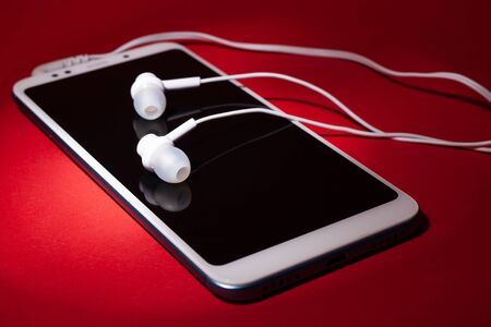 Concept: listen to  music from the phone.Smartphone with plug-in headphones on a red background.closeup Stok Fotoğraf