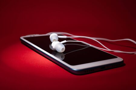 Concept: listen to music from the phone with headphones on a red background close up.