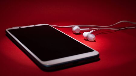 Concept: listen to music from the phone. Smartphone with headphones in the rays of light on a red background closeup