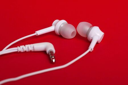 Concept: white headphones (earphones) on a red background close-up