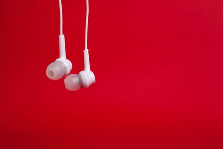Hanging  white headphones (earphones) on a red background  with copyspace closeup Stok Fotoğraf