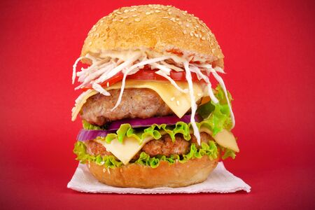 Meat burger with cheese and vegetables on a red background.Double cheeseburger with fresh tomatoes, lettuce, onions, and chopped cabbage close-up Stock Photo - 129841365