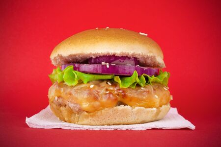 Big cheeseburger with fresh lettuce, onion rings and cream cheese on a meat patty on a red background closeup Stock Photo - 129841363