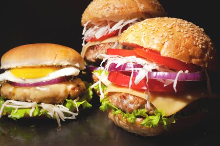 Concept: fast food big burgers on a black table. Large double cheeseburger with beef cutlets and fresh vegetables, composition: pepper, onion, tomatoes,egg, salad, cheese on a dark background.closeup Stock Photo - 129841366