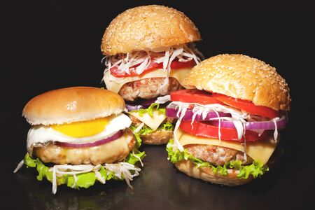 Concept: fast food big burgers on a black table. Large double cheeseburger with beef cutlets and fresh vegetables, composition: pepper, onion, tomatoes,egg, salad, cheese on a dark background.close-up Stock Photo - 129841367