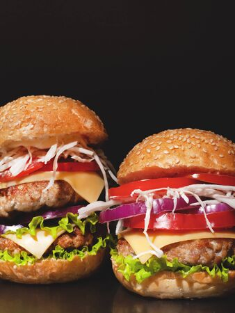 Concept: fast food big burgers on a black table. Two double cheeseburger with beef cutlets and fresh vegetables, composition: pepper, onion, tomatoes,egg, salad, cheese on a dark background.closeup Stock Photo