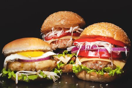 Concept: fast food big burgers on a black table. Large double cheeseburger with beef cutlets and fresh vegetables, composition: pepper, onion, tomatoes,egg, salad, cheese on a dark background.closeup Stock Photo - 129841371