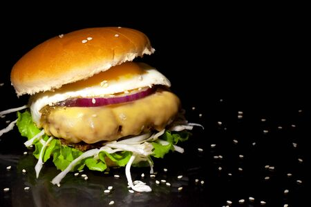 Fast food concept: juicy fat burger with a large patty, egg, lettuce, cream cheese, onion rings and sesame seeds on a dark background closeup Stock Photo - 129841374