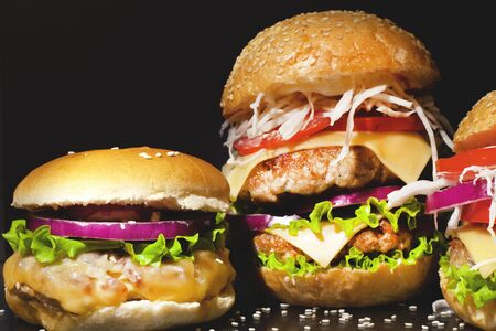 Fast food concept: fat burgers with cheese and vegetables on a dark background closeup Stock Photo - 129841375