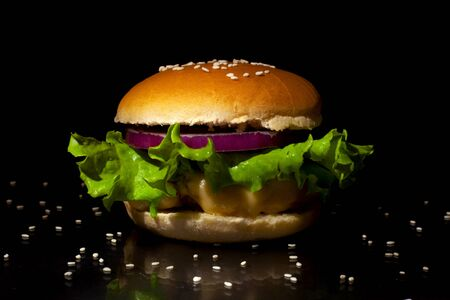 Fast food concept: Burger with cutlet, cheese, onions and lettuce on a black background closeup Stock Photo - 129841384