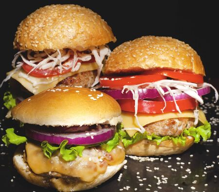 Fast food concept: fat burgers with cheese and vegetables on a dark background.homemade cheeseburgers close up .