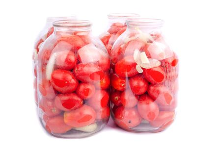 red homemade tomatoes in jars on a white background closeup
