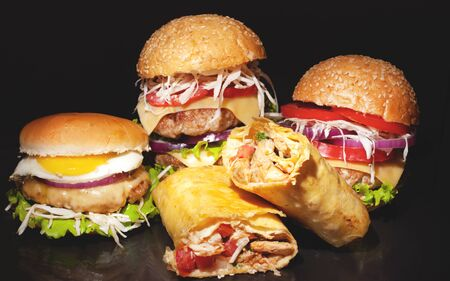 street fast  food concept on a dark bakground,burgers with meat and vegetables, shawarma with chicken closeup