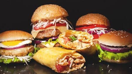 Fast food concept on a dark bakground,burgers with meat and vegetables, shawarma with chicken.fatty junk food close-up