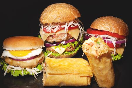 Street fast  food concept on a dark bakground, big double burgers with meat and vegetables, shawarma with chicken close up Stock Photo