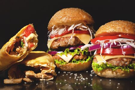 street fast  food concept on a dark bakground,burgers with meat and vegetables and sesame seeds, shawarma with chicken closeup