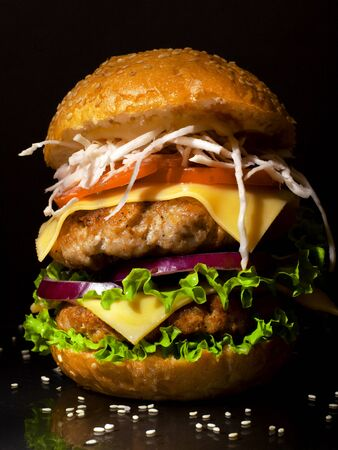 huge homemade burger with two cutlets and fresh vegetables on a dark background closeup Stock Photo - 129841415