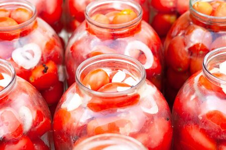 pickled (canned) tomatoes in jars close up.fermentation of tomatoes