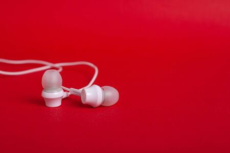 White headphones (earphones) on a red background with copy space close up