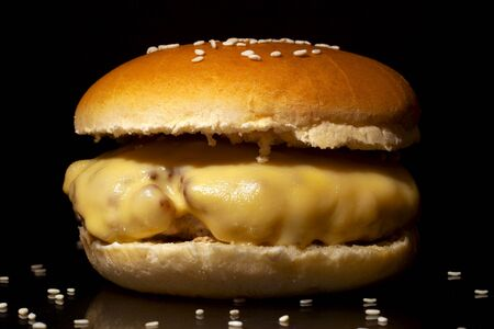 Concept: dark fast food photography.Hamburger with cheese and sesame seeds on  a dark background close-up