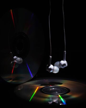 cd compact disk and white headphones on a dark background. concept: listen to rap music  close-up