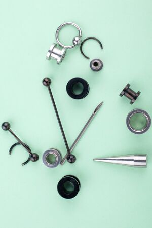 set of piercing accessories, earrings, tunnels, bars for stylish people closeup vertical.