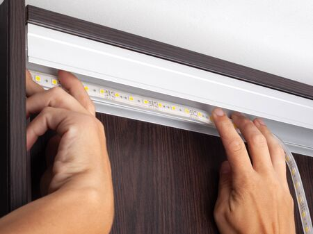 Electrician hands install LED strip lighting  in the niche of the cabinet to illuminate the wardrobe.