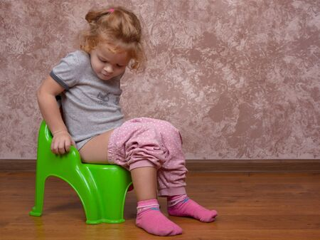 little girl sitting on the potty,the child learns to go to the toilet on pot