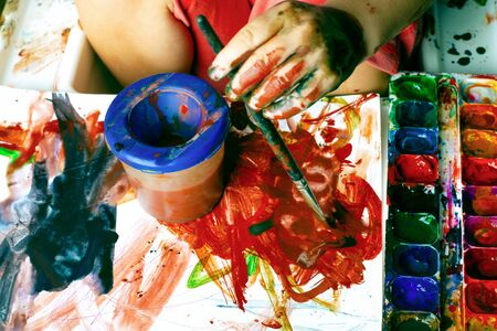 little girl draws with watercolors,the child got dirty with colorful paints, drawing on paper.