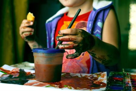 Little girl got dirty in watercolor.a child learns to paint with colorful paints.
