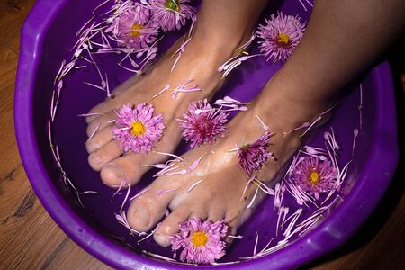 beauty female legs in a bath with flowers,aroma spa with medical herbs.