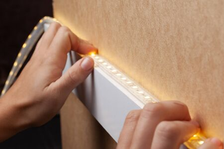 the master glues the LED strip into the niche of the shelf from the cabinet for lighting.installation of diode lighting tape.