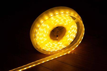 LED strip for decorative lighting,Diode led tape on dark background logo. 스톡 콘텐츠