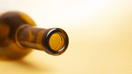 empty wine bottle on a yellow background closeup.