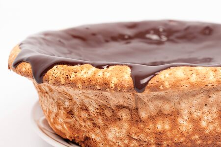 flowing chocolate on the sides of the cake. sponge cake with caramel pouring around the edges on white background close up. Banco de Imagens