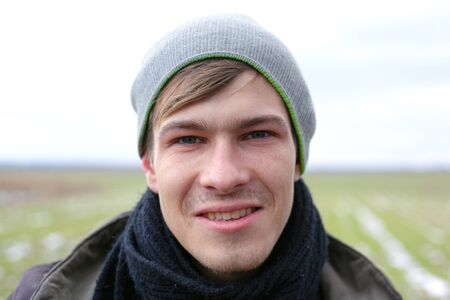 young handsome unshaven guy close-up face portrait on a spring field background with green grass.