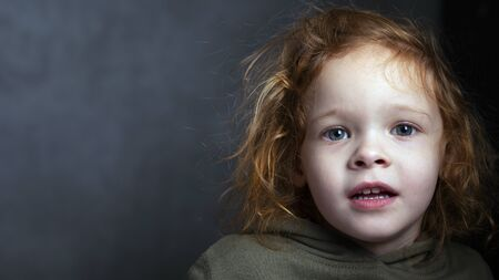 cute red-haired little girl portrait on a gray background. redhead child .