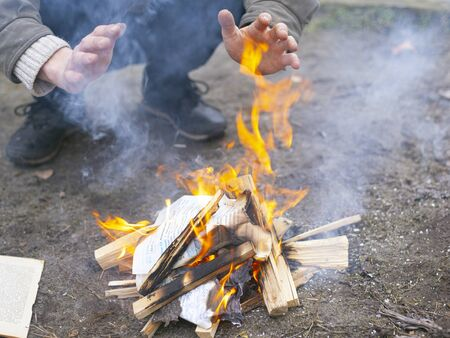man warms himself by the fire, camping bonfire. Banque d'images