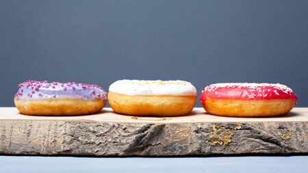 three assorted glazed donuts of different colors on a wooden plank on a gray background. Stockfoto