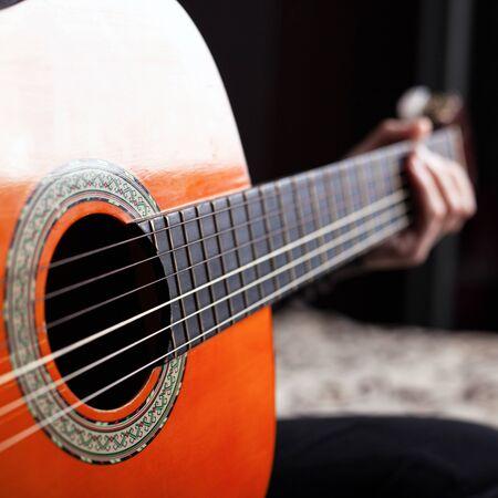 hand on fretboard acoustic guitar orange color.