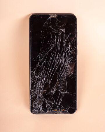 broken touchscreen black phone, smartphone, broken glass display smartphone on a beige background.