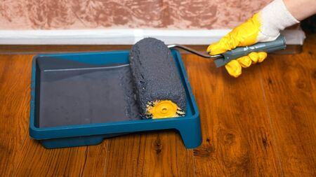 master in yellow glove dips roller in a tray with gray paint for painting walls.repairs.