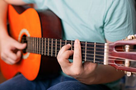 guy plays acoustic guitar, man finger holding a bar chord. learn to play a musical instrument. Stockfoto