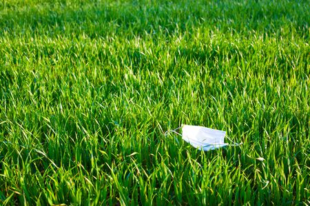 medical mask lying on the green grass. Used contaminated garbage is released into the environment during the pandemic of the coronavirus covid-19. Фото со стока