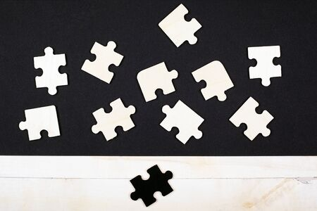 white wooden puzzles on a black background and one black puzzle on a white background close-up top view. White crow antisocial different leadership skills talented outcast children's educational toy.